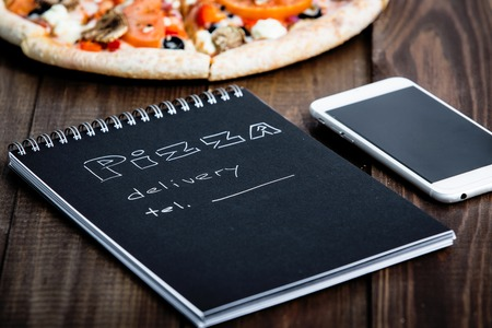 dinner menu: Close-up of pizza, a mobile phone and a notebook with the text: Pizza delivery. background wooden table. Notebook black with white text