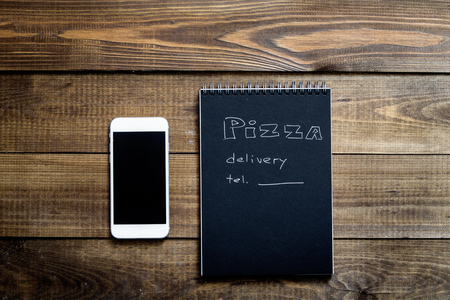 Close-up of mobile phone and notebook with the text: Pizza delivery. background wooden table. Notebook black with white text