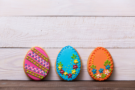 gingerbread: Colourful tasty Easter cookies in a row on white wooden background Stock Photo