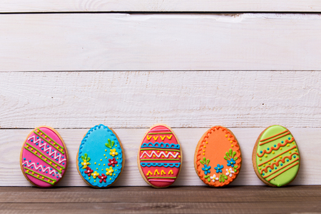 Colourful tasty Easter cookies in a row on white wooden background Archivio Fotografico