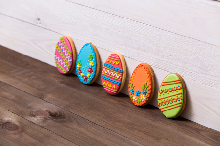 Colourful tasty Easter cookies in a row on white wooden background Standard-Bild