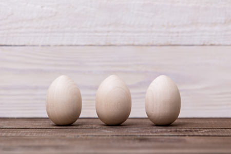 Happy easter! Wooden eggs on a wooden background. Easter conceptual background