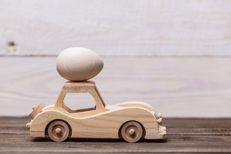 Happy easter! Wooden toy retro car carries eggs on a wooden background. Easter conceptual background Archivio Fotografico