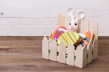 Colourful tasty Easter cookies and bunny on white wooden background Standard-Bild