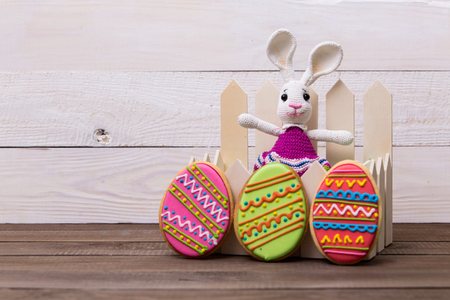 Colourful tasty Easter cookies and bunny on white wooden background Archivio Fotografico
