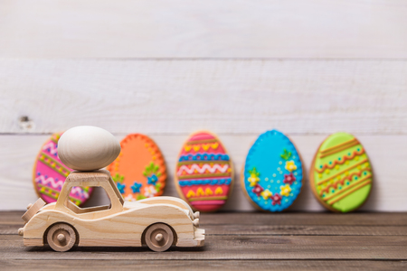 Happy easter! Wooden toy retro car carries eggs on a wooden background. Easter conceptual background