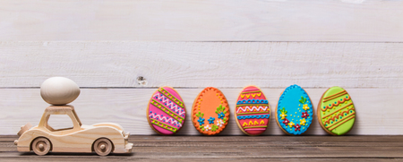 Happy easter! Wooden toy retro car carries eggs on a wooden background. Easter conceptual background Standard-Bild