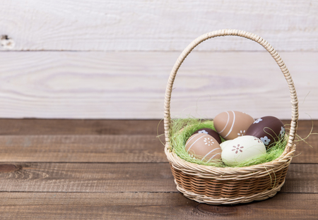 Happy easter! Beautiful Easter eggs are decorated in bed colors in a basket on a wooden background. Easter conceptual background. Archivio Fotografico