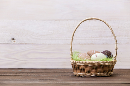 Happy easter! Beautiful Easter eggs are decorated in bed colors in a basket on a wooden background. Easter conceptual background. Standard-Bild