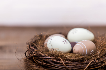 Happy easter! Beautiful Easter eggs are decorated in bed colors in a nest on a wooden background. Easter conceptual background.