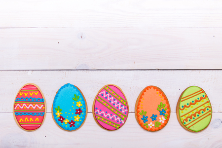 Delicious Easter cookies background. Colorful Easter cookies all over white wooden background. Eggs with different pattern icing. Top view