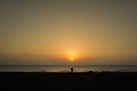 one person silhouette in front of sunrise in jeju island Stock Photo