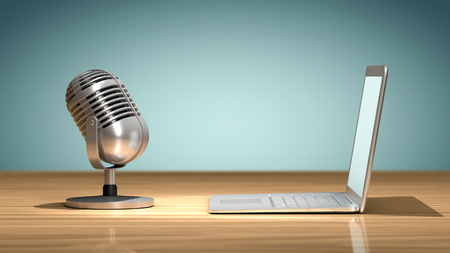 Vintage microphone in front of a laptop on a wooden table and oriented to record the sound. Concept of numerical recording or multimedia