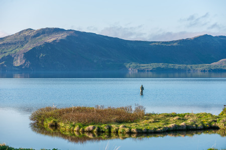 Candid view of fisherman in Thingvellir Lake, Iceland. photo