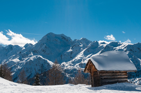 Wooden hut covered with snow in front of high mountains.