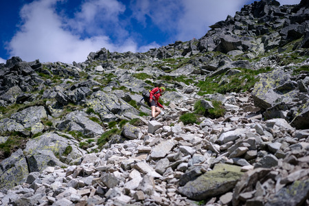 Young woman descending in a difficult mountain terrain. Hiking in High Tatras National Park, Slovakia.