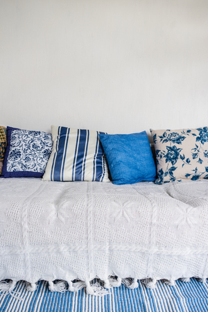 clean carpet: Detail view of white couch with many pillows and bluewhite carpet in front. Clean white wall. Interior design concept.