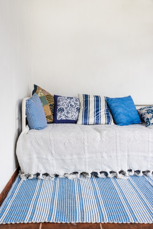 clean carpet: Vertical view of white couch with many pillows and bluewhite carpet in front. Clean white wall. Interior design concept.