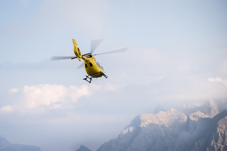 Medical rescue helicopter in air. Italian Dolomites.