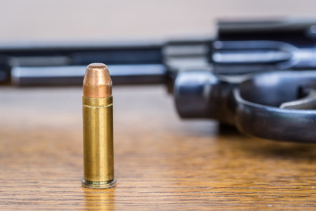 Close up view of bullet and handgun. Shallow depth of field. Pistol out of focus. Vertical view.
