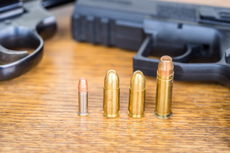 Close up view of different type of bullets and handgun. Shallow depth of field. Pistol out of focus.
