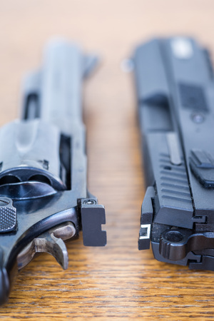 Close up view of handgun. Revolver and pistol side by side. Shallow depth of field.