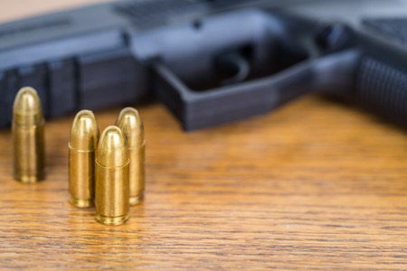 Close up view of bullets and handgun. Shallow depth of field. Pistol out of focus.