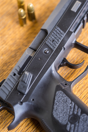 Close up view of bullets and handgun. Shallow depth of field. Pistol out of focus. Vertical view. Stock Photo