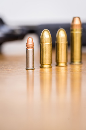 Close up view of different type of bullets and handgun. Shallow depth of field. Pistol out of focus. Vertical view.