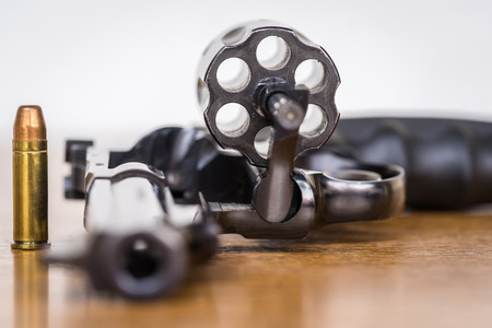 Close up view of bullet and handgun. Shallow depth of field. Focus on a bullet. Vertical view. Stock Photo
