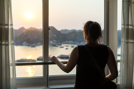 Young female looking out of window. Female tourist looking at bay out of a hotel window. Beautiful evening light.