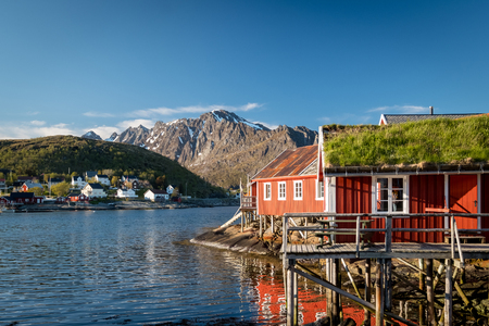 Red Classic Norwegian Rorbu fishing huts with sod roof on Lofoten islands. Norwegian traditional type of house used by fishermen