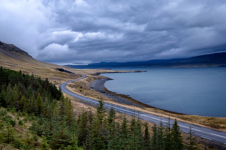 Scenic view of dramatic icelandic landscape with empty road next to a fjord. Banco de Imagens