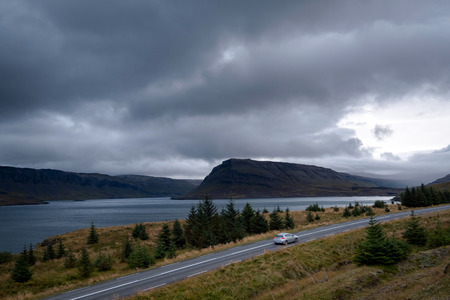 Scenic view of dramatic icelandic landscape with single silver car on a road in motion.