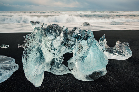 Ice on the black volcanic beach near Jokulsarlon glacier lagoon, winter Iceland. Stock Photo