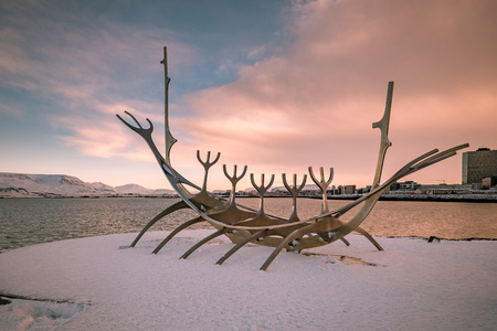 Sun Voyager monument, landmark of Reykjavik city with sea and mountains in background, Iceland during sunset.