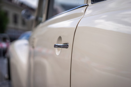 A close up look at an old classic white car. Retro automobile exterior scene. Old vehicle.