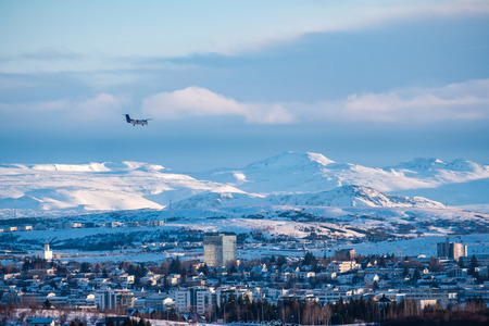 The plane is landing in a Reykjavik downtown in a golden evening light. Capital city of Iceland Reykjavik in winter surrounded with snow covered mountains.