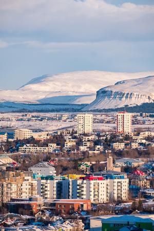 Vertical view of Reykjavik downtown in a golden evening light. Capital city of Iceland Reykjavik in winter surrounded with snow covered mountains.