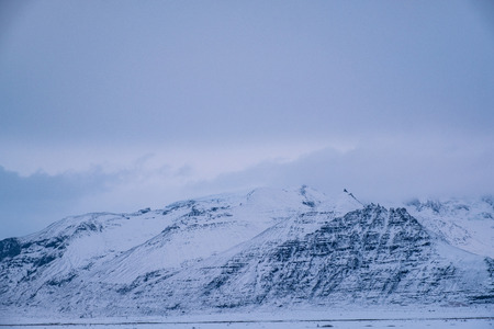 Dramatic icelandic landscape with snow covered mountains. Cold winter day in Iceland. Stok Fotoğraf