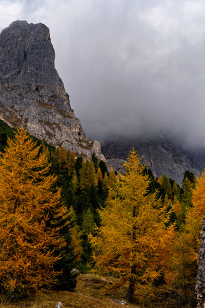 Colorful scenic view of majestic Dolomites mountains in Italian Alps. Majestic rocky mountains surrounded with yellow trees in autumn time.