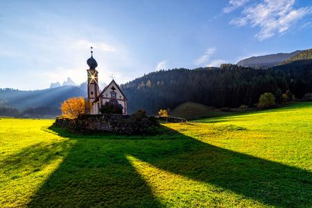 Wonderful Sunny Landscape of Dolomite Alps. St Johann Church, Santa Maddalena, Val Di Funes, Dolomites, Italy. Fairy velley in Dolomites mountains under sunlit. Amazing nature Background. Stock Photo