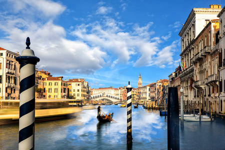 Traditional Gondola on famous Canal Grande with Rialto Bridge in background during beautiful summer day in Venice, Italy.