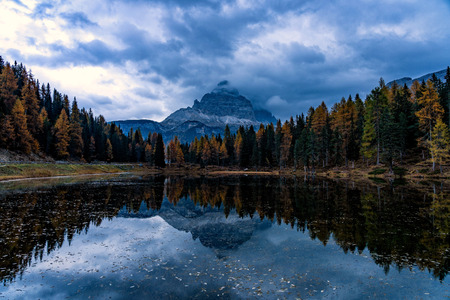 Autumn landscape of Antorno lake with famous Dolomites mountain peak of Tre Cime di Lavaredo in background in Eastern Dolomites, Italy Europe. Beautiful nature scenery and scenic travel destination in autumn colors.