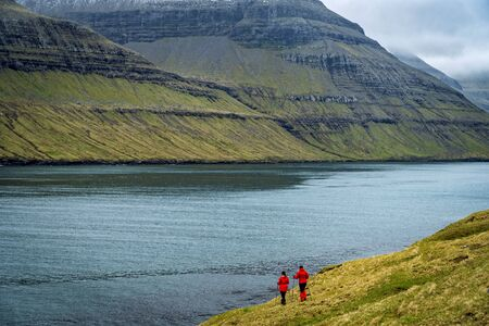 Two female hikers walking on a trail next to a wide fjord in Faroe Islands.