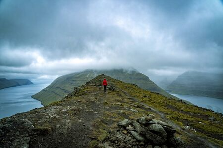 Young female hikers walking on a trail next to a wide fjord in Faroe Islands. Banco de Imagens