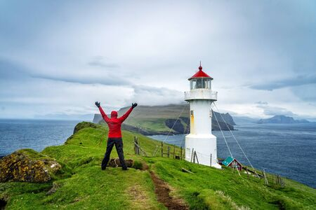 Young female hiker enjoying a spectacular view of lighthouse on Mykines island in Faroe Islands. Фото со стока