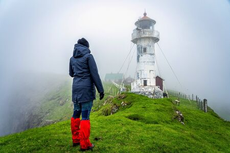 Young female traveler admiring dramatic landscape of Faroe Island. White lighthouse in middle of green meadows in a foggy weather.
