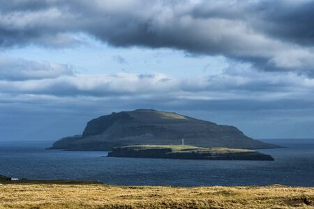 Dramatic landscape of Faroe Islands with grass meadows and rocky cliffs in stormy weather. Banco de Imagens