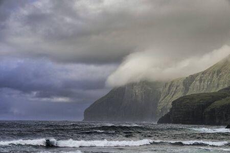 Landscape of giant sea cliffs overlooking the ocean in Faroe Islands.